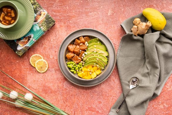 Salmon and mango poke bowl in a grey plate with a red background