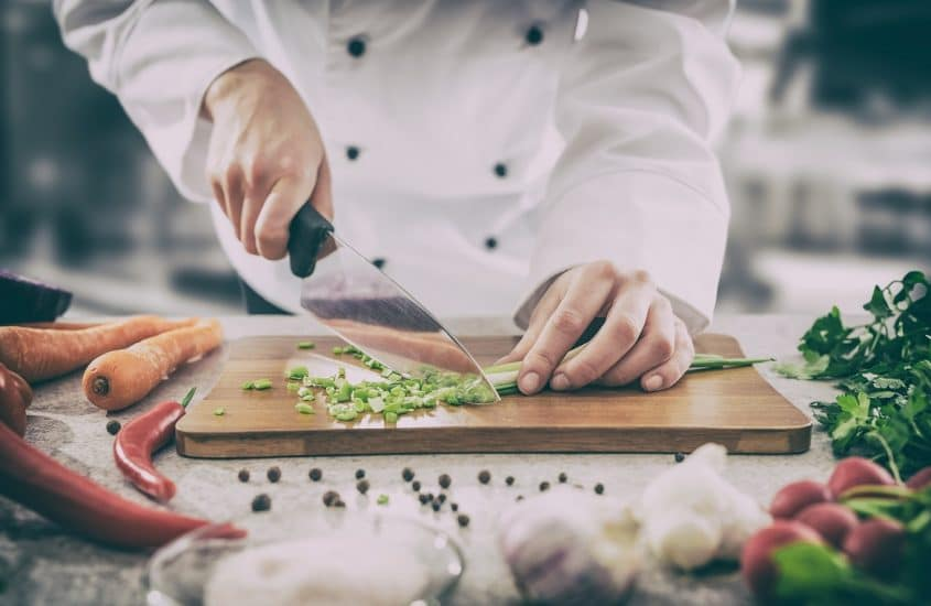 Chef cutting vegetables on a cutting table