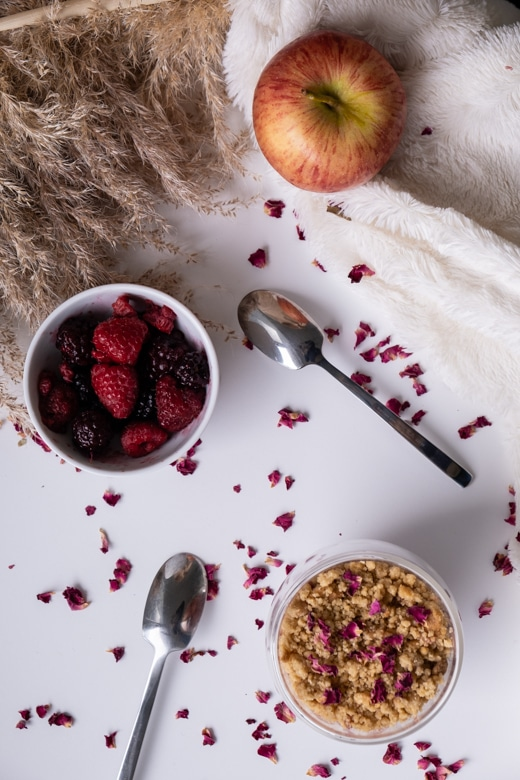 Apple and red fruits crumble on a white table