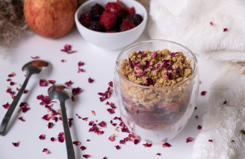 Apple and red fruits crumble on a white table with decoration