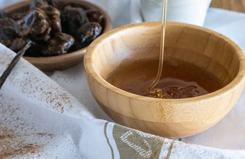 Ingredients to substitute sugar like honey, dates, vanilla laid on a table