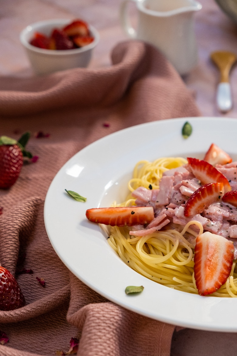 Strawberry carbonara on a plate with decoration around