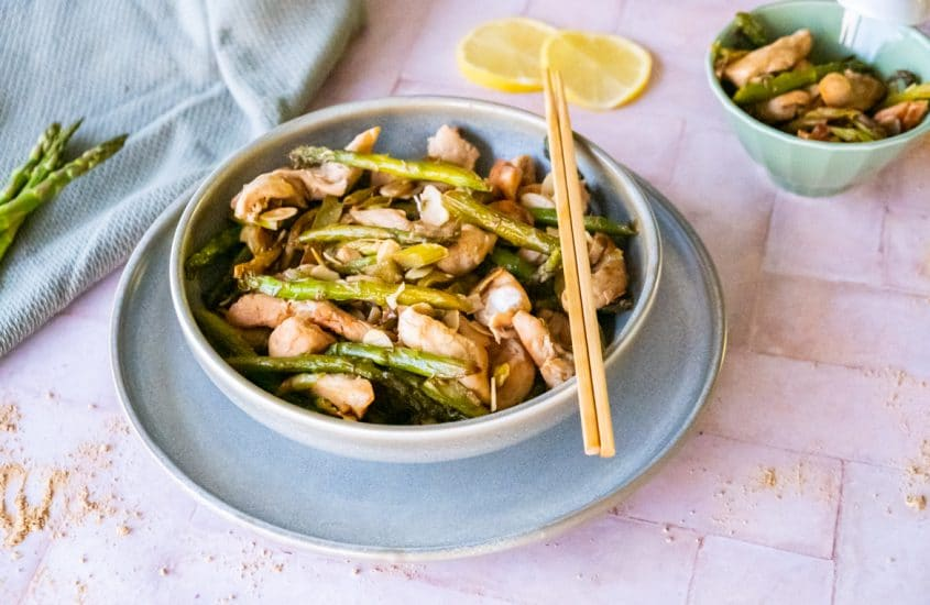 Wok of green asparagus with chicken and grilled almonds in a bowl