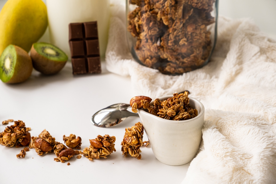 Homemade granola presented in a cup on a white table, large view