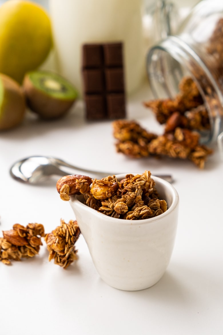 Homemade granola presented in a cup on a white table, vertical view