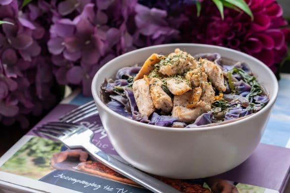 Spinach and cabbage chicken with coconut milk recipe in a bowl laid on a table
